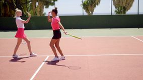 Triumphant young female tennis player. Cheering and walking across court as she wins the game and match stock footage