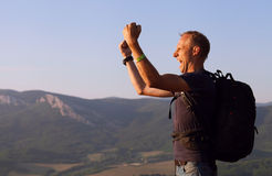 Triumphed hiking traveller on the top of mountain Royalty Free Stock Image