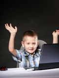 Triumphing child with a laptop computer Royalty Free Stock Image