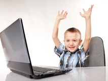 Triumphing child with a laptop computer isolated Stock Images