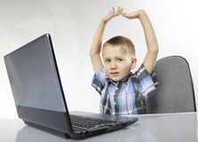 Triumphing child with a laptop computer Stock Photography