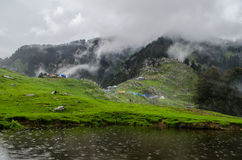 Triund Hill. A view of triund hill in monsoon with clouds over dhauladhar mountain range Stock Photos