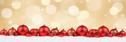 Triunfo de oro de la nieve del fondo de la decoración roja de la bandera de las bolas de la Navidad imagenes de archivo