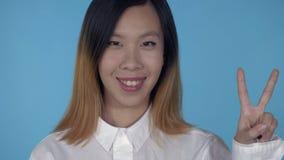 Triunfo femenino feliz coreano del gesto que muestra almacen de video