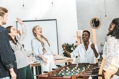triunfo multicultural feliz de la celebración de los colegas mientras que juega a fútbol de la tabla imagen de archivo