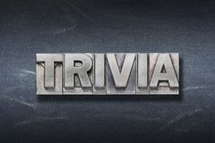 Trivia word den. Trivia word made from metallic letterpress on dark jeans background royalty free stock image