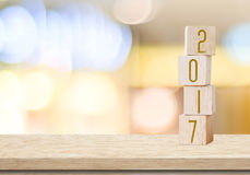 Träkuber med 2017 på tabellen över suddighetsbokehbakgrund som är ny Arkivfoto
