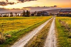 Träladugård med lantbrukarhemmet på solnedgången i Norge Arkivfoto