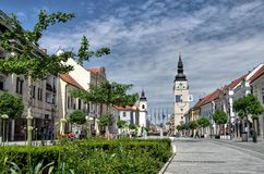 TRNAVA, SLOVAKIA  Local and visitor stroll the Trojicne square, near the city tower, In Trnava, Slovakia Stock Photo