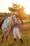 Trocas de carícias da moça do jóquei e aperto do cavalo branco no por do sol da noite Alargamento de Sun Foto de Stock