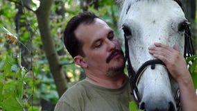 Trocas de carícias de sorriso consideráveis do homem seu cavalo bonito filme