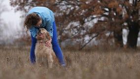 Trocas de carícias fêmeas novas alegres seu cão bonito fora vídeos de arquivo