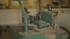 Trociny dmuchający zdala od starej maszyny dla musztrować wokoło dziury w drewnianej desce w meblarskim warsztacie zbiory wideo