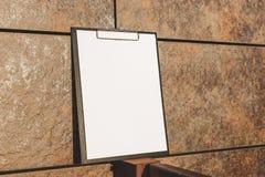 Trocista acima da tabuleta para o papel contra a parede imagem de stock