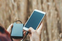 Trocista acima do telefone e do banco na mão de uma menina, na perspectiva de um campo amarelo fotografia de stock royalty free