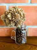 Trockenblumen bündeln mit Kaffee im Glasvase gegen Backsteinmauerhintergrund Lizenzfreie Stockbilder
