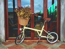 Trockene Blumen im Korb und im netten Fahrrad auf dem netten Boden Lizenzfreie Stockfotografie