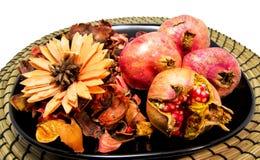 Trockene Blumen, Trockenblumengesteck und Granatäpfel auf einer schwarzen Scheibe und einer hölzernen Platte Für Wellness und ent Lizenzfreie Stockfotos