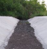 Trockene Entwässerungswasserstraße mit schwarzem Boden Stockfotos