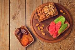 Trockene Früchte und Nüsse auf Holztisch Ansicht von oben Lizenzfreie Stockfotos