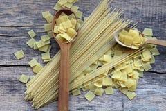 Trockene gelbe Teigwaren des Quadrats in einer Mischung mit langen Spaghettis auf und nahe den hölzernen Löffeln lizenzfreie stockbilder