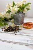 Trockene grüne Teeblätter des Jasmins mit Jasminblumen Lizenzfreie Stockbilder
