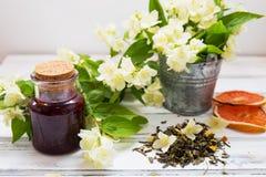 Trockene grüne Teeblätter des Jasmins mit Jasminblumen und Himbeermarmelade Lizenzfreie Stockfotos