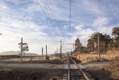 Trockene Landschaft mit ländlichen Schotterstraße-Überfahrt-Eisenbahnlinien Lizenzfreies Stockbild