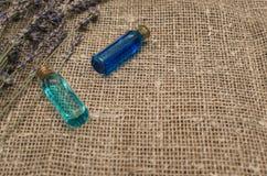 Trockene Lavendelblumen und blaue ätherische Öle auf dem Sackleinenleinwandhintergrund mit Kopienraum lizenzfreies stockbild
