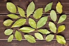 Trockene Olivgrünlorbeerbaumblätter auf braunem Holz stockfoto