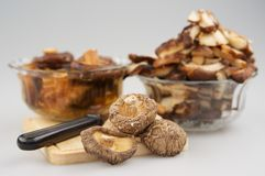 Trockene Pilz oder lentnus Shitake edodes und Messerplatz auf hackendem Brett lassen Unschärfepilz tränken und Stück des Pilzes e stockfotos