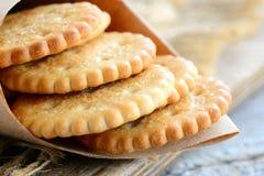 Trockene salzige Crackerplätzchen in einem Packpapier Knusprige wohlschmeckende Crackersnackidee für Kinder oder Erwachsene rusti Lizenzfreie Stockfotografie