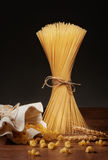 Trockene Spaghettis, cavatappi Teigwaren und Weizenähren auf Holztisch Lizenzfreie Stockfotos
