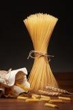 Trockene Spaghettis, penne rigate Teigwaren und Weizenähren auf Tabelle Lizenzfreie Stockbilder