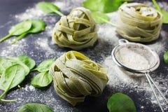 Trockene Spinatsteigwaren, frischer Spinat und Mehl Stockfotografie