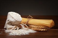 Trockene Teigwaren, Tasche des Mehls und Weizenähren auf Tabelle Stockfoto