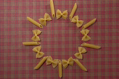 Trockene Vollkorn-penne und Fliegenteigwaren auf rotem quadratischem Hintergrund Flache Lage Beschneidungspfad eingeschlossen Kop Stockfotografie