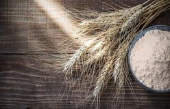 Trockene Weizenähren und Mehl des Hintergrundes auf altem Holztisch Stockfotografie
