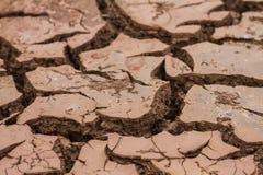 Trockener Boden und gebrochener Boden knackt tief Erde im roten Land als Symbol des heißen Klimas und der Dürre lizenzfreie stockbilder