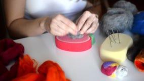 Trockener Filzstoff: die Frau verteilt die Fasern des Graufilzes, um die gewünschte Form zu geben Vorlagenklasse auf der Schaffun stock video footage