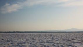 Trockener Salzsee mit einem Windmühlenbauernhof auf dem Hintergrund stock footage