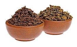 Trockener schwarzer und grüner Tee in einem Lehmcup Stockbild