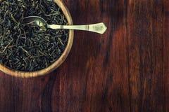 Trockener Tee in der hölzernen Platte auf Holztisch Stockbild