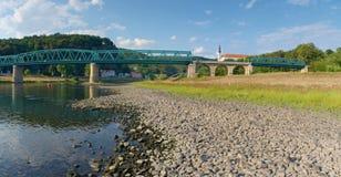 Trockenes Flussbett von Fluss Elbe in Decin, Tschechische Republik Schloss über alter Eisenbahnbrücke stockfotos