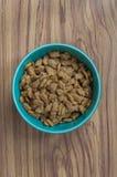 Trockenes Katzenfutter in der grünen Schale Lizenzfreie Stockbilder