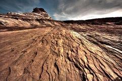 Trockenes Wüstenland unter bewölktem Himmel Stockbild
