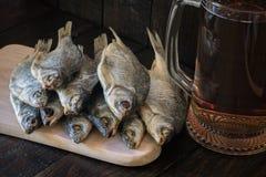 Trockenfisch auf einem hölzernen Brett und einem Becher Bier auf einem hölzernen Hintergrund lizenzfreie stockbilder