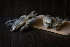 Trockenfisch auf einem hölzernen Brett und auf einem hölzernen Hintergrund stockfotos
