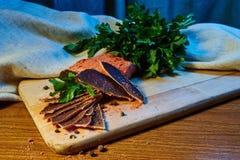 Trockenfleisch, basturma liegt auf einem hölzernen Brett mit Kapriolen und Gewürzen Frische Petersilie lizenzfreies stockfoto