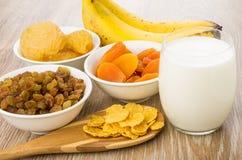 Trockenfrüchte, Löffel mit Corn Flakes, Bananen und Glasmilch Stockfotos
